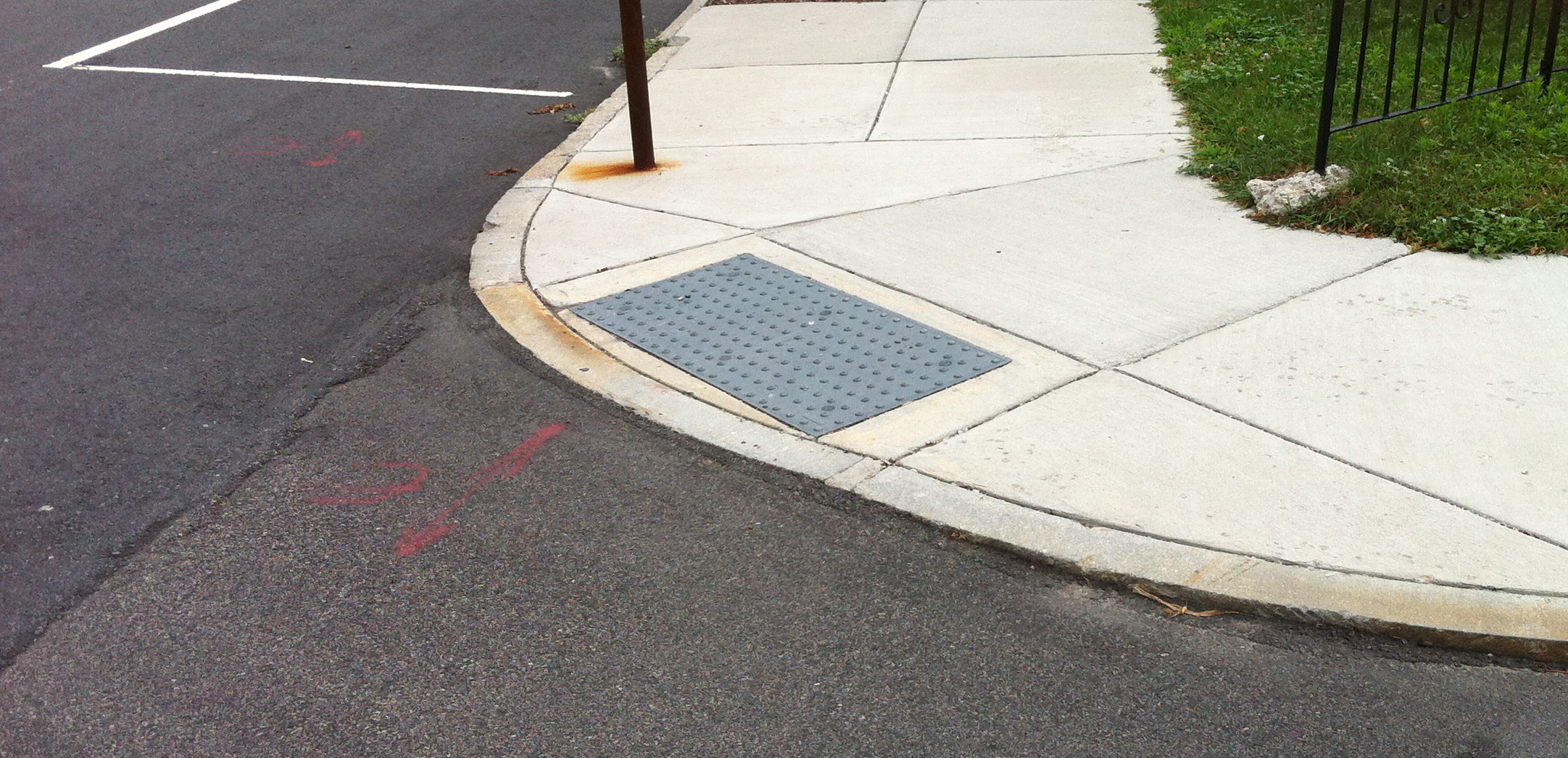 a generic looking curb cut. it's a wedge cut into the sidewalk to allow wheelshairs to move between the sidewalk and street at an intersection
